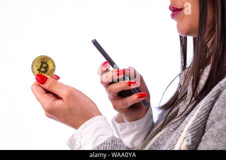 Virtuelle cryptocurrency Geld Bitcoin goldene Münze in der linken Hand einer Frau mit rotem Nagellack. Schöne weibliche Modell lächelnd. Die Zukunft des Geldes - Stockfoto