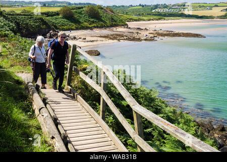 Zwei Frauen Wanderer zu Fuß auf eine Promenade auf Wales Küstenweg in der Nähe von Lligwy, Isle of Anglesey, Wales, Großbritannien, Großbritannien - Stockfoto