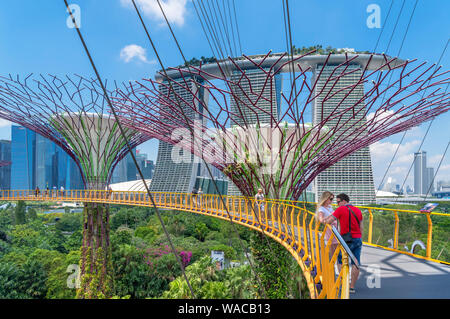 Die ocbc Skyway, eine Antenne Gehweg in der Supertree Grove, mit Blick auf die Marina Bay Sands, Gärten durch die Bucht, Singapore City, Singapur