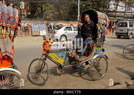 Pedicab driver für die Passagiere auf der belebten Straße im Thamel Bezirk von Kathmandu, Nepal warten
