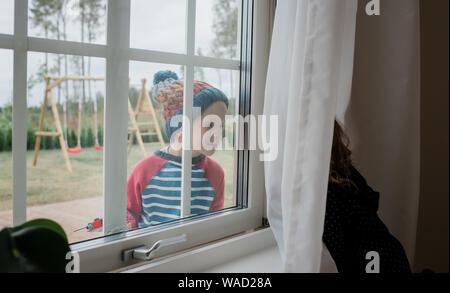 Junge Blick durch das Fenster auf seine Schwester lächelnd