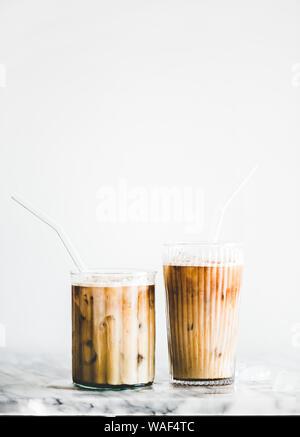 Hausgemachte Iced Latte Kaffee in Gläser mit Strohhalmen auf Tisch - Stockfoto