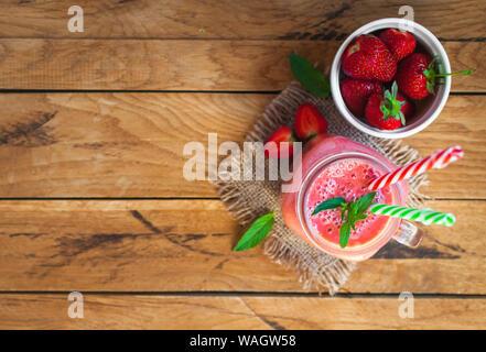 Strawberry Smoothie in einem Glas mit frischer Minze, auf hölzernen Hintergrund, Ansicht von oben, Text, kopieren Raum - Stockfoto