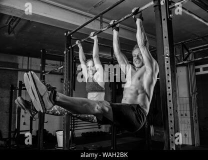 Ein Paar mittleren Alters tut ein Fitness Training zusammen und Spaß haben. Muskulöse Mann und Frau tun die Übung l auf der horizontalen Leiste sitzen. - Stockfoto