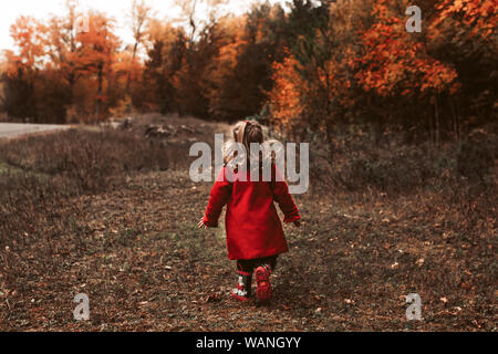 Kind zu Fuß außerhalb das Tragen der roten Mantel auf einen schönen Herbst Tag - Stockfoto