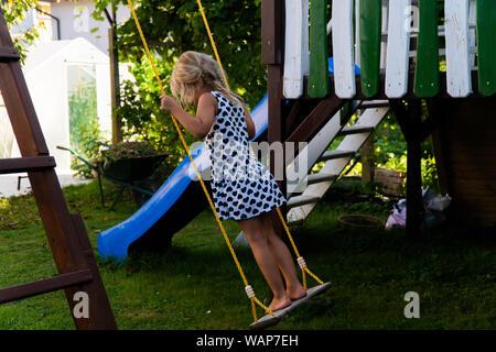3-5 jährige blonde Mädchen Spaß haben auf einer Schaukel im Freien. Sommer Spielplatz. Mädchen Schwingen hoch. Junge Kind auf der Schaukel im Garten - Stockfoto