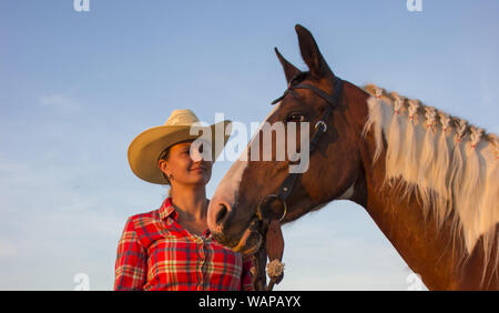 Junge Mädchen und ihre Stute mit Pigtails auf Mähne - Stockfoto