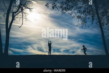 Silhouette Schatten von zwei Kindern auf einem Hügel mit einem blauen Himmel hinter ihnen beim Spielen - Stockfoto