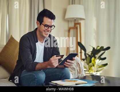 Fröhlicher Mann im Wohnzimmer shopping online mit Kreditkarte sitzen - Stockfoto