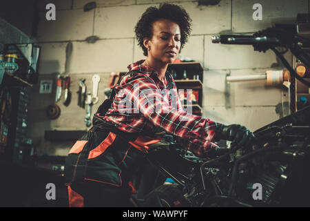Afrikanische amerikanische Frau Mechaniker reparieren ein Motorrad in einem Workshop.