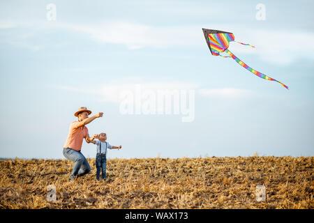 Vater mit Sohn starten farbenfrohe, Drachen auf dem Feld. Konzept einer glücklichen Familie Spaß im Sommer Aktivität - Stockfoto