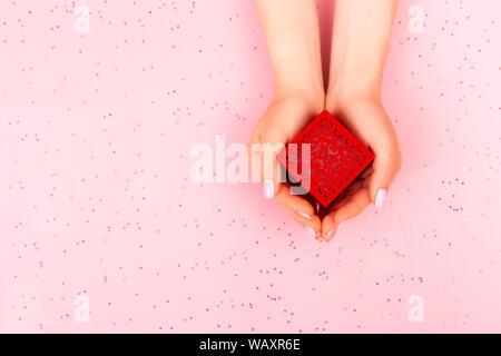 Roter Geschenkbox in weibliche Hände auf einem farbigen Hintergrund der Ansicht von oben. - Stockfoto