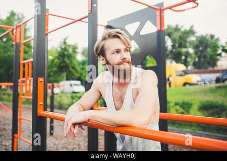 Portrait von Müde Athlet am Gym. Müde Mann hängen von der Bar. Erschöpft Athlet im Fitnesscenter zu trainieren. Zeit zum Ausruhen. Lange Training ist vorbei. Muskulös - Stockfoto