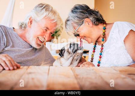 Portrait von älteren Reifen Kaukasier, Paar mit lustigen Haustier mops Hund küssen und haben Spaß zusammen mit Liebe und Glück - Begriff des Tieres - Stockfoto