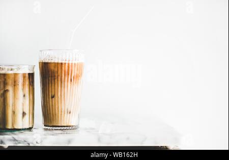 Iced Latte Kaffee in Gläser mit Strohhalmen auf Tisch, Nahaufnahme - Stockfoto
