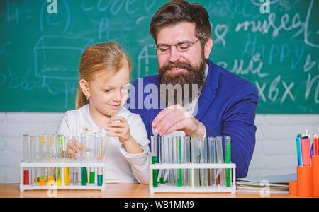 Wie Interesse Kinder studieren. Faszinierende Chemie Lektion. Man bärtige Lehrer und Schüler mit Reagenzgläsern im Klassenzimmer. Privatunterricht. Schule Chemie Experiment. Chemie zu erklären Kid. - Stockfoto