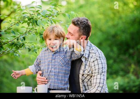 Glückliche Familie zusammen. Die Entwicklung des Kindes. Sohn und Vater essen Milch Brei. happy Vatertag. Kleiner Junge mit Vati outdoor. Kindheit Glück. Gesunde Ernährung und Diät. Tag der Familie. Die Qualität von Lebensmitteln. - Stockfoto