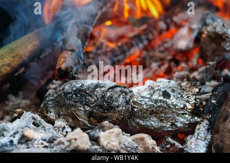 Gebackene Kartoffeln auf dem Feuer, Gemüse in Folie im Feuer - Stockfoto
