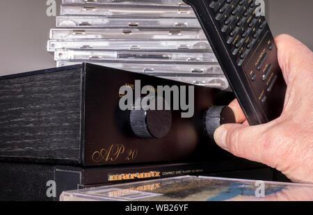 Eines Mannes Hand, die eine Fernbedienung beim Drehen ein Rotary Volume Regler auf einem traditionellen analogen/analoge Verstärker, mit CDs übereinander gestapelt. - Stockfoto