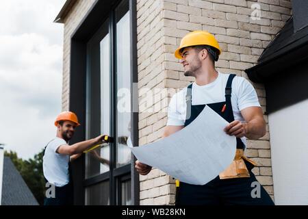 Selektiver Fokus der glücklichen Architekt holding Blaupause in der Nähe von Kollegen - Stockfoto