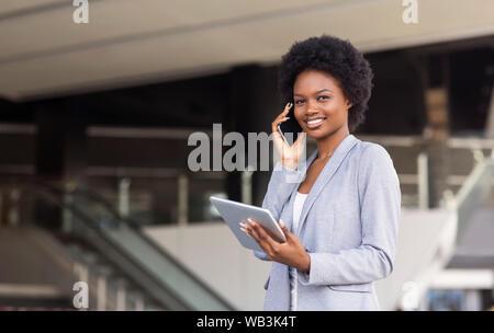 Junge Frau mit Handy, mit digitalen Tablet in der Nähe von modernes Bürogebäude - Stockfoto
