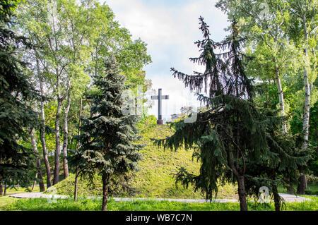 Christliche Kreuz auf einem grünen Hügel Hügel unter einem bewölkten Himmel an einem sonnigen Tag - Stockfoto