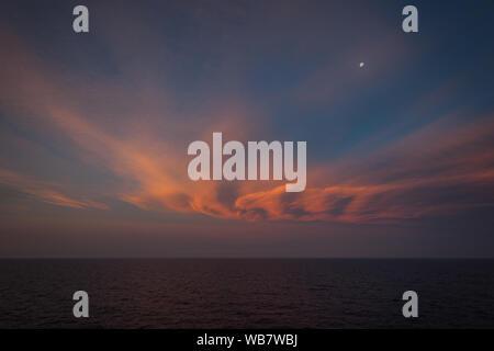 Mond über dem Meer und orange-farbige Wolken nach Sonnenuntergang - Stockfoto