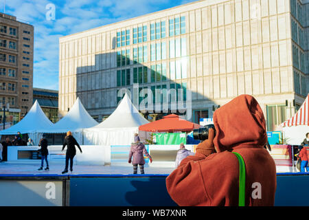 Frau Fotos machen und tun Schlittschuhlaufen auf der Eisbahn im Winter am Weihnachtsmarkt in Berlin in Deutschland. Urlaub Tag mit Schlittschuhen auf dem Alexanderplatz - Stockfoto