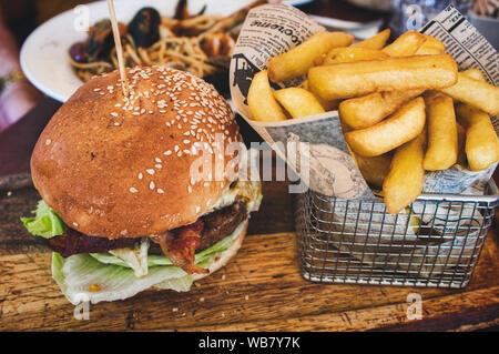 Burger und Pommes frites/Chips in einem Korb auf einem Holzbrett in einem Restaurant