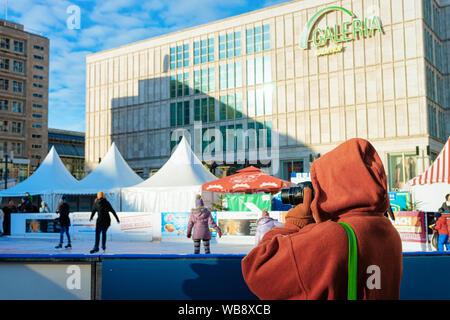 Berlin, Deutschland - Dezember 8, 2017: Frau Fotos machen und tun Schlittschuhlaufen auf der Eisbahn im Winter am Weihnachtsmarkt in Berlin in Deutschland. Urlaub Tag mit Schlittschuhen auf dem Alexanderplatz - Stockfoto