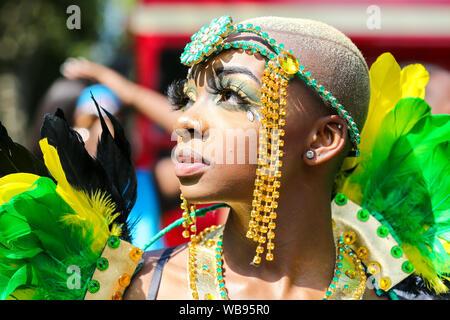Tänzerin in einem Kostüm während die Kinder Parade auf die Familie Tag der Notting Hill Carnival in London. Tausende von Nachtschwärmern in Notting Hill Carnival, Europas größtem Straßenfest und eine Feier der Karibischen Traditionen und kulturellen Vielfalt der Hauptstadt. - Stockfoto