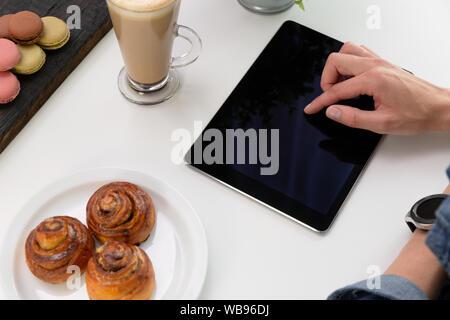 Frau mit über Tablet smartwatch im Coffee Shop. Kaffee und Gebäck, Makronen auf weißer Tisch. Freie Arbeiten - Stockfoto
