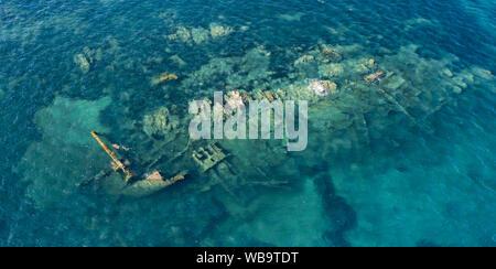 Ansicht von oben, beeindruckende Luftaufnahme eines Wracks im Meeresschutzgebiet von Tavolara. Einige Leute Schnorcheln in einem smaragdgrünen Meer. - Stockfoto