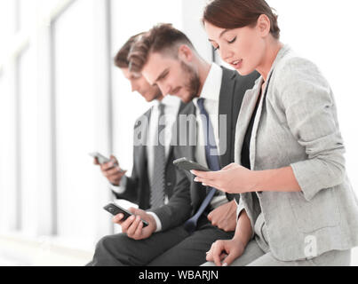 Gruppe der jungen Menschen mit Gadgets in einer Reihe sitzen. - Stockfoto