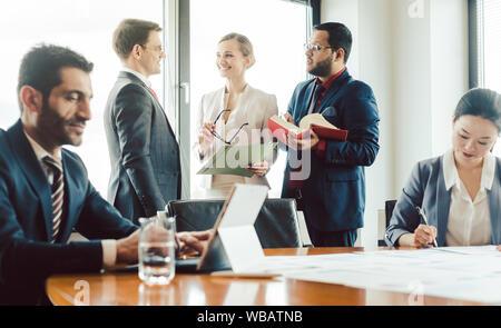 Türkische Geschäftsleute Arbeiten am Laptop mit Kollegen im Hintergrund - Stockfoto