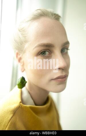 Junge Frau mit Ohrring aus rohen Zucchini - Stockfoto
