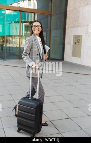 Attraktive glückliche junge asiatische Geschäftsfrau tragen Anzug im Freien in der Innenstadt, die Koffer und Zeitung - Stockfoto
