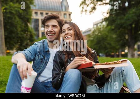 Foto von fröhlichen jungen Freunde Verliebten in der Natur sitzen Green Park im freien Pizza auf Picknick umarmen Essen. - Stockfoto