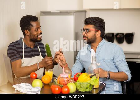 Zwei Studenten argumentieren, was für das Abendessen zu kochen. Multikulturelle Freunden in der Küche sitzt, mit laptop computer Sprechen und Vorbereitung von Salat, smo - Stockfoto