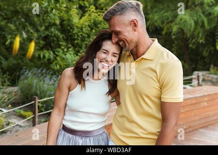 Portrait von freudiger im mittleren Alter Paar Mann und Frau lachend und Umarmen beim Gehen im Sommer Park - Stockfoto