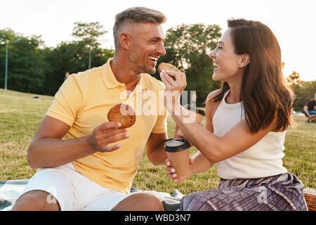 Portrait von Mitte überrascht - gealterte Ehepaar Mann und Frau trinkt Kaffee zum Mitnehmen und essen Cookies beim Sitzen auf Gras im Park - Stockfoto