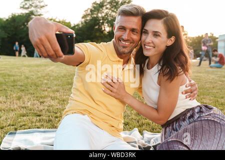 Portrait von lächelnden nach paar Mann und Frau umarmt und unter selfie Foto auf Handys während der Sitzung auf Gras im Park - Stockfoto
