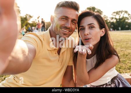 Portrait von gerne Paare mittleren Alters, Mann und Frau, die selfie Foto und Senden von Luft küssen, während im Sommer Park - Stockfoto