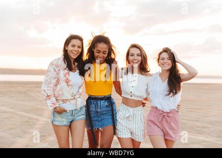 Foto der jungen optimistischen fröhlichen Frauen Mädchen Freunde gehen im Freien am Strand. - Stockfoto