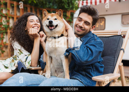 Bild der romantischen lächelndes Paar Mann und Frau in der Nähe von Anhänger mobile home Ihr Hund umarmt. - Stockfoto