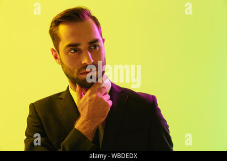 Bild der nachdenkliche junge Geschäftsmann im Anzug sein Kinn berühren isoliert auf gelbem Hintergrund - Stockfoto