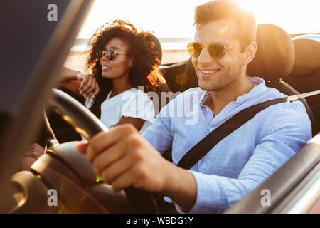 Schönen lächelnden Jungen multiethnischen Paar reiten in eine Wandelanleihe - Stockfoto