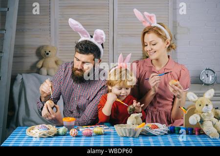 Frohe Ostern! Familie, Mutter, Vater und Kind Spaß malen und dekorieren Eier für den Urlaub - Stockfoto