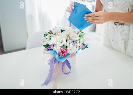 Frau öffnet Umschlag mit Karte im Blumenstrauß in Geschenkbox auf Küche links. Lassen Sie sich überraschen. Für Urlaub präsentieren. Blume Lieferung - Stockfoto