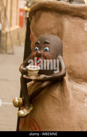Skulptur von einzigartigen und komische Kaffeebohne Charakter holding Tasse Kaffee und auf Sack mit Kaffeebohnen sitzt - Werbemittel Display außerhalb der City Cafe - Stockfoto